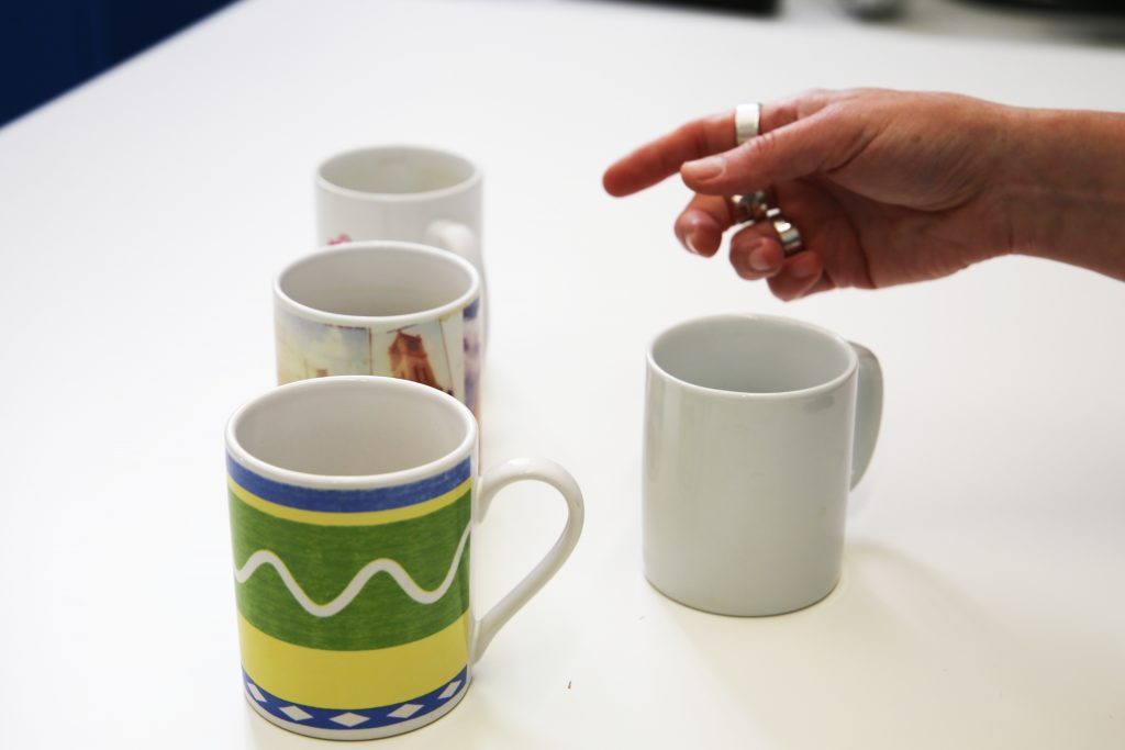 Someone choosing between similar but different coffee mugs